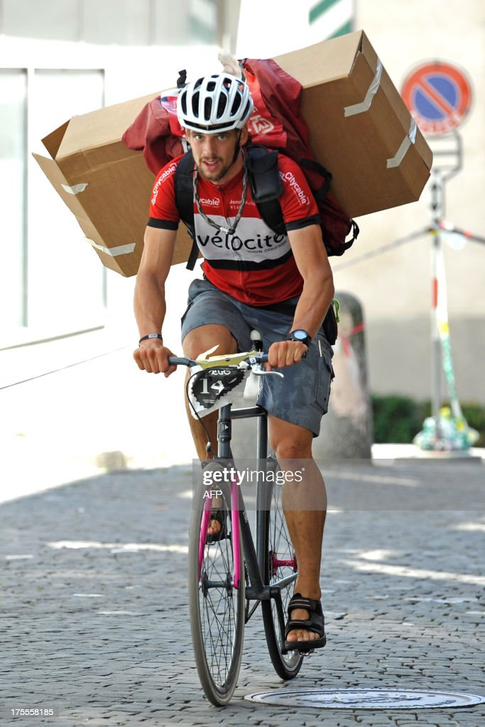 Jonas Vuille of Switzerland rides with a cargo parcel to the second place during the Bike Messenger World Championships in Lausanne on August 4, 2013. Some 400 runners from 40 different countries took part in the competion. AFP PHOTO / Harold Cunningham