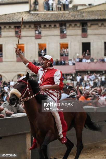Jonatan Bartoletti known as Scompiglio celebrates after winning the historical Italian horse race of the Palio of Siena on July 2 2017 in Siena / AFP...
