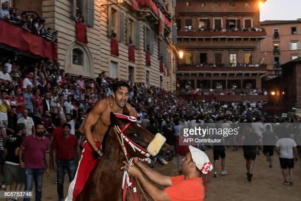 Jonatan Bartoletti known as Scompiglio celebrates on his horse Sarbana after winning the historical Italian horse race of the Palio of Siena on July...