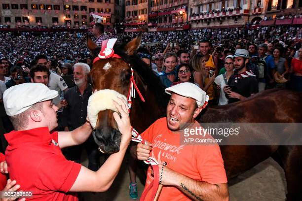 Jonatan Bartoletti's horse Sarbana is hold after winning the historical Italian horse race of the Palio of Siena on July 2 2017 in Siena / AFP PHOTO...