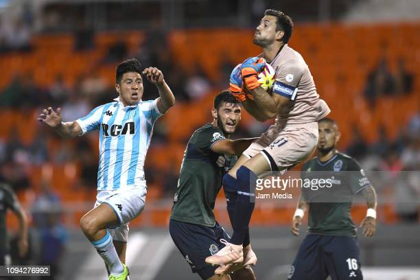 Jonathan Cristaldo of Racing Club fights for the ball with Alexis Arias goalkeeper of Gimnasia during a friendly match between Racing Club and...