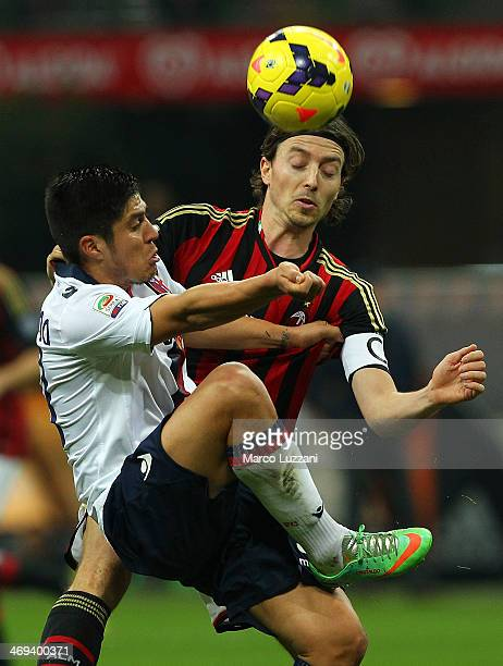 Jonatan Ezequiel Cristaldo of Bologna FC competes for the ball with Riccardo Montolivo of AC Milan during the Serie A match between AC Milan and...