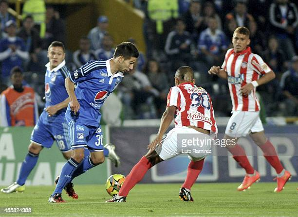 Jonathan Agudelo of Millonarios struggles for the ball with Johnny Ramirez of Junior during a match between Millonarios and Junior as part of Liga...