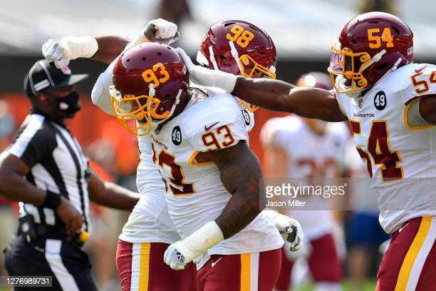 Jonathan Allen of the Washington Football Team celebrates with his teammates Matthew Ioannidis and Kevin Pierre-Louis after sacking Baker Mayfield of...