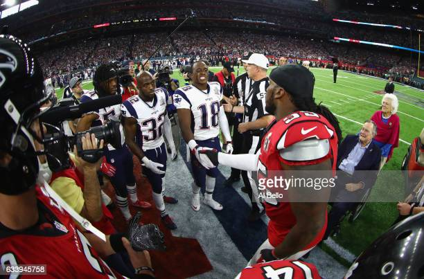 Jonathan Babineaux of the Atlanta Falcons shakes hands wiith Matthew Slater of the New England Patriots ahead of the coin toss during Super Bowl 51...
