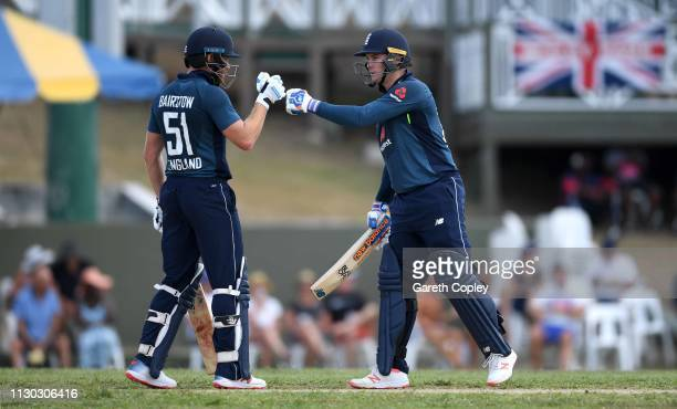 Jonathan Bairstow and Jason Roy of England punch gloves during the One Day Tour Match between England and The University of West Indies Vice...