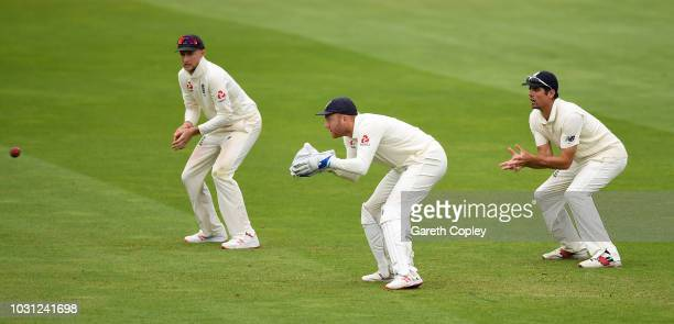 Jonathan Bairstow of England keepes wicket alongside Joe Root and Alastair Cook during day five of the Specsavers 5th Test match between England and...