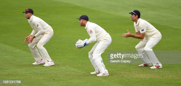 Jonathan Bairstow of England keeps wicket alongside Joe Root and Alastair Cook during day five of the Specsavers 5th Test match between England and...