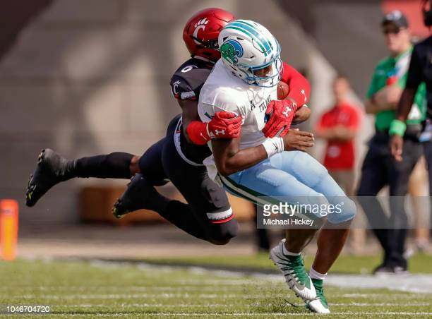 Jonathan Banks of the Tulane Green Wave is tackled from behind by Perry Young of the Cincinnati Bearcats at Nippert Stadium on October 6, 2018 in...