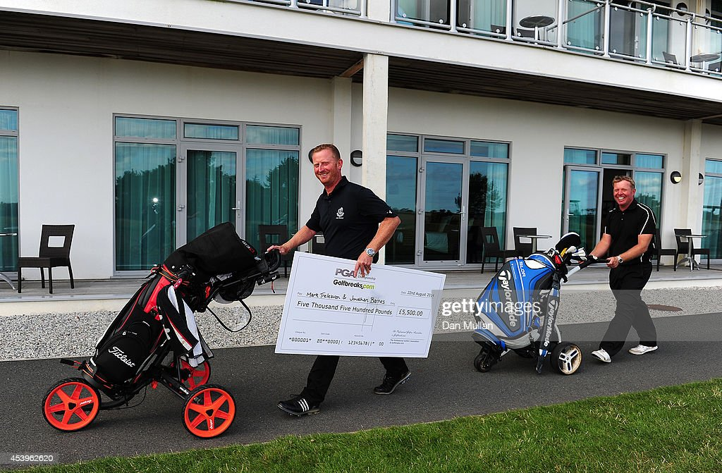 Jonathan Barnes (R) of Lee-on-The-Solent Golf Club and Mark Treleaven of Hayling Golf Club leave the course with their cheque after being crowned champions during day three of the Golfbreaks.com PGA Fourball Championship at St. Mellion International Resort on August 22, 2014 in Saltash, England.