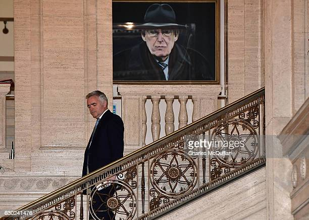 Jonathan Bell makes his way past a painting of the late DUP leader Ian Paisley at Stormont on December 19 2016 in Belfast Northern Ireland Mr Bell is...