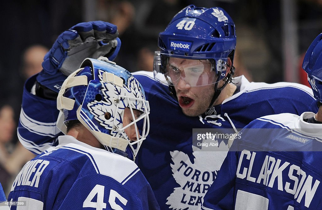 Jonathan Bernier #45 and Troy Bodie #40 of the Toronto Maple Leafs celebrate a win over the Vancouver Canucks during NHL game action February 8, 2014 at the Air Canada Centre in Toronto, Ontario, Canada.