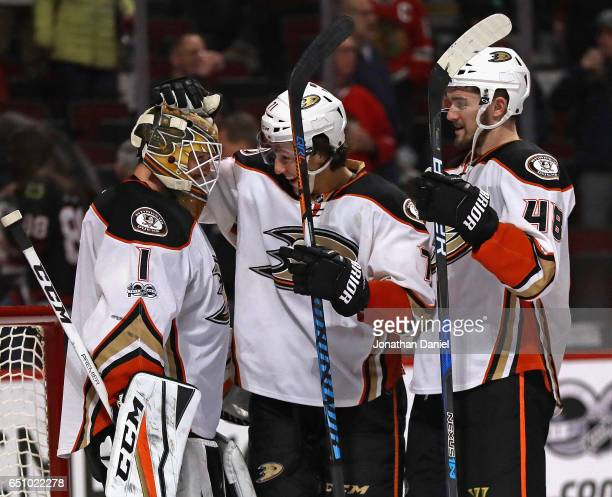 Jonathan Bernier of the Anaheim Ducks is congratulated by Brandon Montour and Logan Shaw after a shutout win against the Chicago Blackhawks at the...