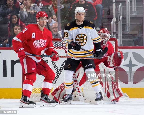 Jonathan Bernier of the Detroit Red Wings follows the play as teammate Dylan Larkin defends against Charlie Coyle of the Boston Bruins during an NHL...