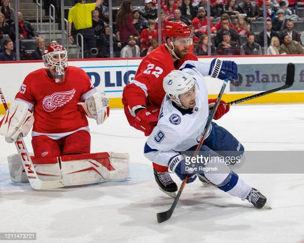 Jonathan Bernier of the Detroit Red Wings follows the play as teammate Patrik Nemeth battles for position with Tyler Johnson of the Tampa Bay...