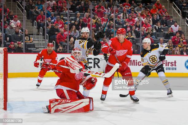 Jonathan Bernier of the Detroit Red Wings makes a blocker save as teammate Gustav Lindstrom battles in front of the net with David Krejci of the...