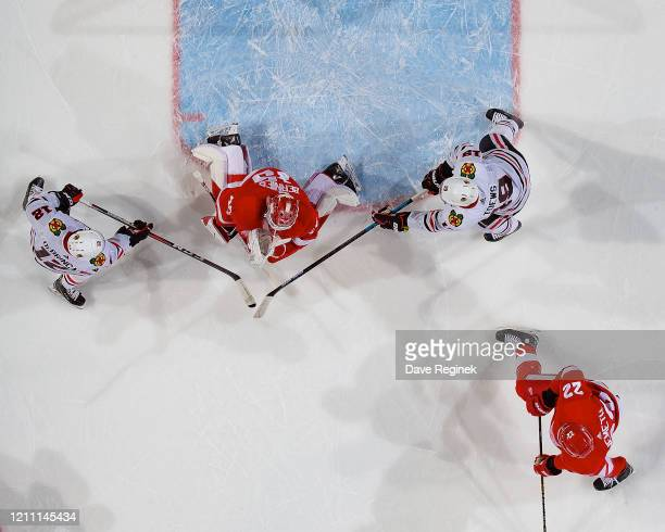 Jonathan Bernier of the Detroit Red Wings makes a save as Alex DeBrincat and Jonathan Toews of the Chicago Blackhawks look for the rebound during an...