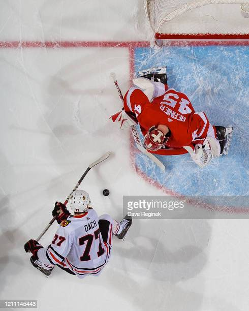 Jonathan Bernier of the Detroit Red Wings makes a save as Kirby Dach of the Chicago Blackhawks looks for the rebound during an NHL game at Little...