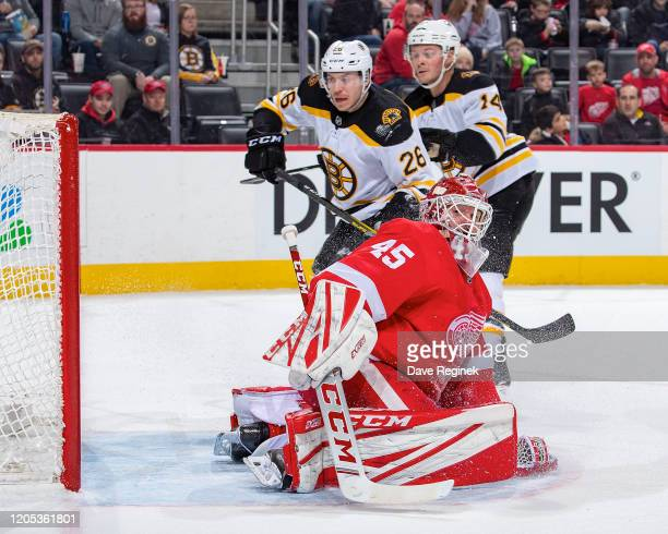 Jonathan Bernier of the Detroit Red Wings makes a save in front of Par Lindholm and Chris Wagner of the Boston Bruins during an NHL game at Little...