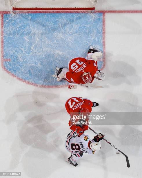 Jonathan Bernier of the Detroit Red Wings reacts to a shot as teammate Filip Hronek battles for position with Ryan Carpenter of the Chicago...