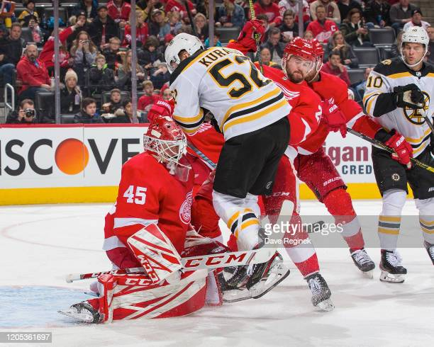 Jonathan Bernier of the Detroit Red Wings reacts to a shot as Sean Kuraly of the Boston Bruins battles in front of the net with Mike Green of the...