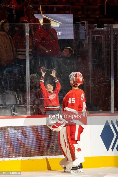 Jonathan Bernier of the Detroit Red Wings skates out the number one star of the game and tosses a stick to a young fan after an NHL game against the...