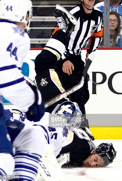 Jonathan Bernier of the Toronto Maple Leafs and Jayson Megna of the Pittsburgh Penguins collide while playing the puck during the game at Consol...