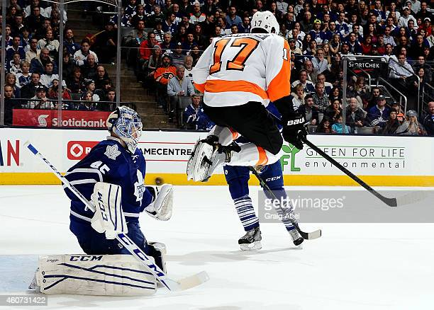 Jonathan Bernier of the Toronto Maple Leafs blocks a screen shot behind a jumping Wayne Simmonds of the Philadelphia Flyers during NHL game action...