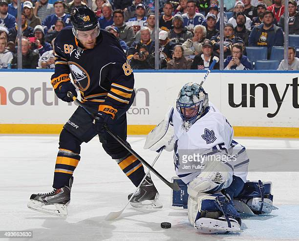 Jonathan Bernier of the Toronto Maple Leafs makes a save alongside Jamie McGinn of the Buffalo Sabres at First Niagara Center on October 21 2015 in...