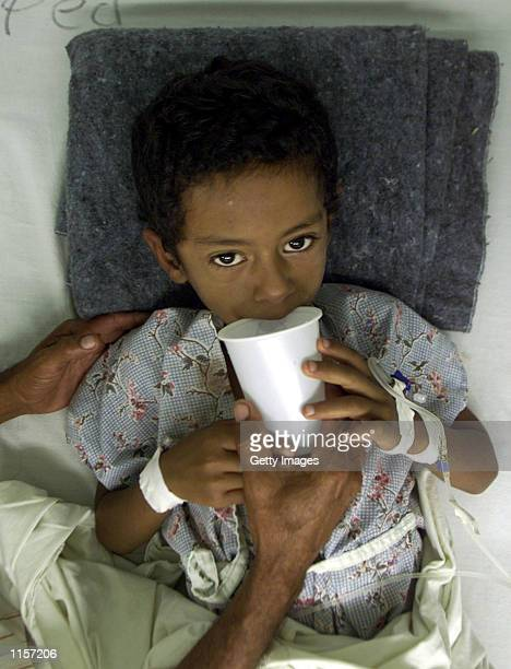 Jonathan Betancort drinks a sip of water while being treated for Hemorrhagic Dengue at the Hospital Escuela July 23 2002 in Tegucigalpa Honduras...
