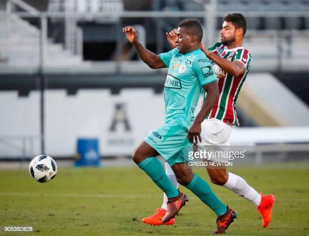 Jonathan Betancurt from Barcelona SC of Ecuador slips the ball past defender Welington Gum Pereira of Brazilian club Fluminense to score the seond of...