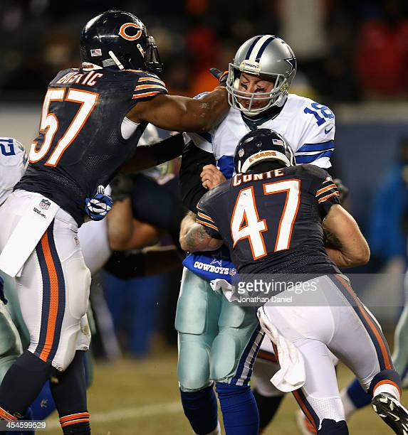Jonathan Bostic and Chris Conte of the Chicago Bears hit Kyle Orton of the Dallas Cowboys after a pass at Soldier Field on December 9 2013 in Chicago...