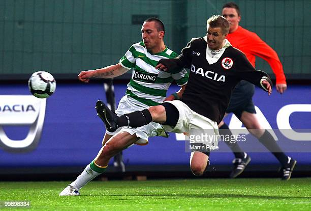 Jonathan Bourgault of St Pauli is challenged by Scott Brown of Celtic during the friendly match between FC St Pauli and Celtic at the Millerntor...