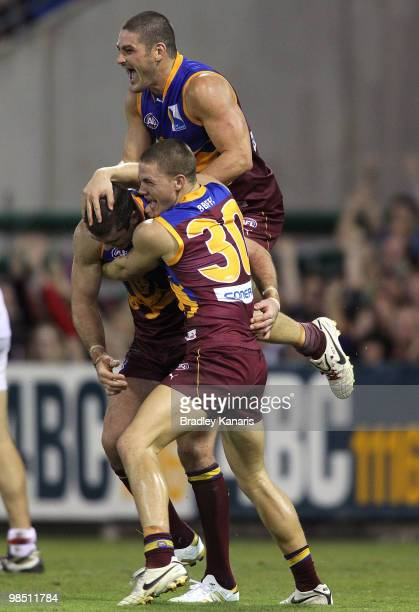 Jonathan Brown of the Lions celebrates with team mates Brendan Fevola and Jack Redden after scoring a goal during the round four AFL match between...