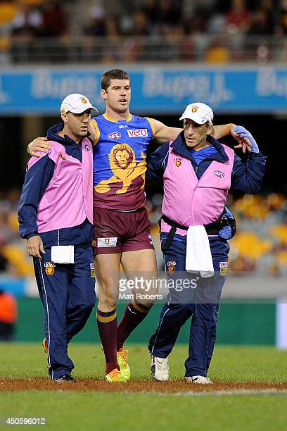 Jonathan Brown of the Lions is assisted from the field during the round 13 AFL match between the Brisbane Lions and the Greater Western Giants at The...