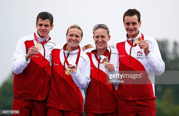 Jonathan Brownlee, Jody Simpson, Vicky Holland and Alistair Brownlee of England pose with their Gold medal on the podium after winning the mixed team...