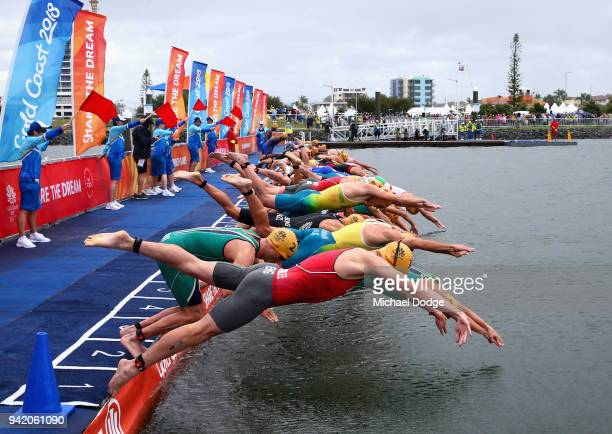 Jonathan Brownlee of England and fellow athletes dive into the water at the start during the Men's Triathlon on day one of the Gold Coast 2018...
