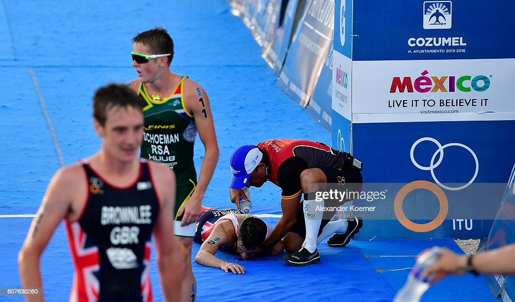 Jonathan Brownlee (r) of Great Britain is helped by medical staff after collapsing of dehydration 200 meters before the finish line of the Men Elite ITU World Championship race at the Fonatur Triathlon Park on September 18, 2016 in Cozumel, Mexico. His brother, Alistair Brownlee, helped Jonathan the last meters to the finish line, as Jonathan could finish second in the race. The medal ceremony was cancelled due to the critical condition of Jonathan Brownlee. The ITU Grand Final World Championship ends tonight.