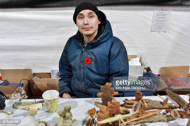 Jonathan C Elias a local carver sells his crafts during the celebration at the Donald Kuptana Sr Arena on November 15 2017 in Tuktoyaktuk Canada The...