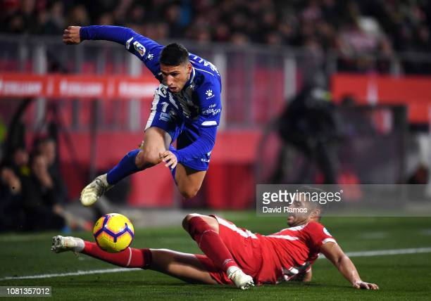 Jonathan Calleri of Deportivo Alaves battles for possession with Juanpe of Girona during the La Liga match between Girona FC and Deportivo Alaves at...
