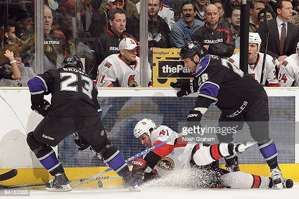 Jonathan Cheechoo of the Ottawa Senators battles to keep control of the puck against Dustin Brown and Jarret Stoll of the Los Angeles Kings during...