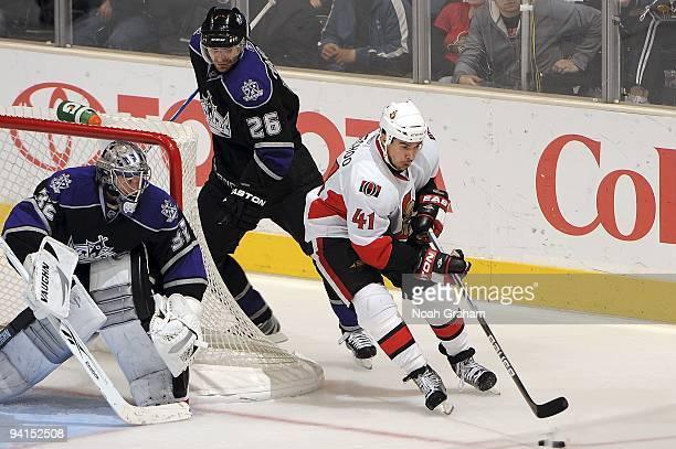 Jonathan Cheechoo of the Ottawa Senators controls the puck outside the crease against Jonathan Quick and Michal Handzus of the Los Angeles Kings...