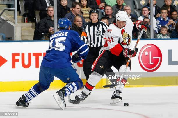 Jonathan Cheechoo of the Ottawa Senators skates against Tomas Kaberle of the Toronto Maple Leafs during the game at Air Canada Centre on October 6...