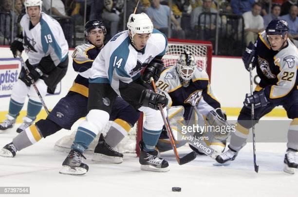 Jonathan Cheechoo of the San Jose Sharks handles the puck against Dan Hamhuis, Greg Johnson and goalie Chris Mason of the Nashville Predators during...