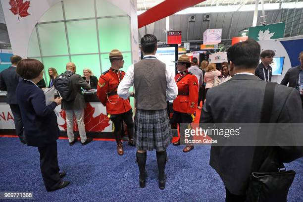 Jonathan Cheng with Scottish Development International Boston center visits the Canadian booth and stands between Royal Canadian Mounted Police...