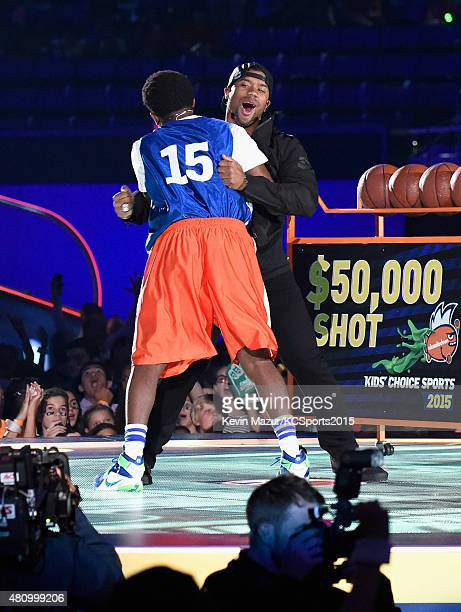 Jonathan Clark and host Russell Wilson celebrate onstage at the Nickelodeon Kids' Choice Sports Awards 2015 at UCLA's Pauley Pavilion on July 16 2015...