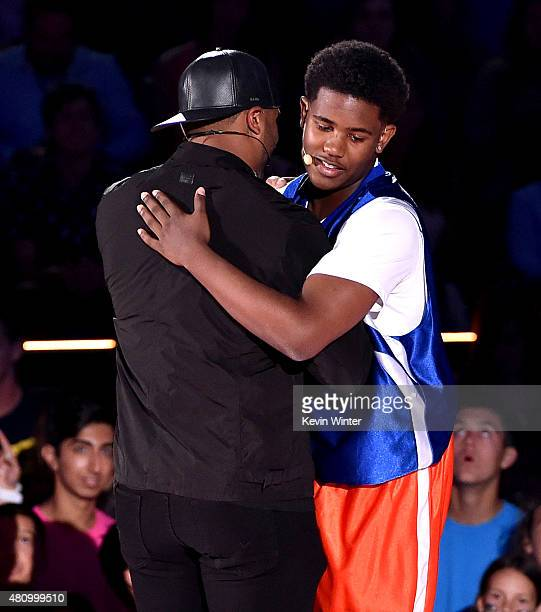 Jonathan Clark winner of the $50000 Shot celebrates with host Russell Wilson onstage at the Nickelodeon Kids' Choice Sports Awards 2015 at UCLA's...