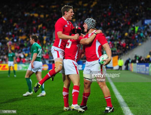 Jonathan Davies of Wales celebrates with teammates Rhys Priestland and Leigh Halfpenny after scoring their third try during quarter final one of the...