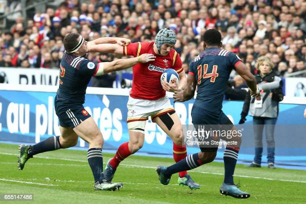 Jonathan Davies of Wales is running with the ball against Guilhem Guirado and Noa Nakaitaci of France during the RBS Six Nations match between France...