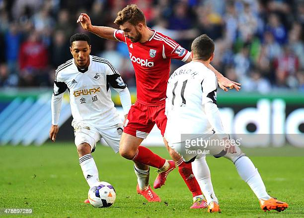 Jonathan de Guzman and Pablo Hernandez of Swansea City battle for the ball with James Morrison of West Bromwich Albion during the Barclays Premier...